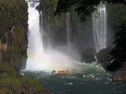 Visitantes en una barca viendo la parte inferior de las cataratas